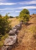 Vieux mur en pierre dans le paysage accidenté images stock