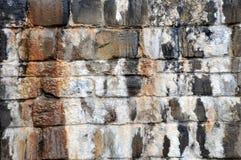 Vieux mur en pierre humide irrégulier avec les marques et les filets humides de l'eau de la chaux minérale calcifiée commençant à images libres de droits