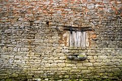 Vieux mur en pierre jaune avec l'hublot proche (3) photos stock
