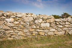 Vieux mur en pierre sur l'herbe Photos stock