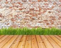 Vieux mur et herbe verte sur le plancher en bois Photos stock