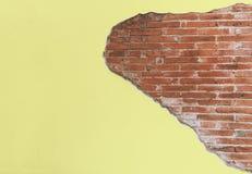 Vieux mur jaune de ciment de fente de vintage avec le bloc de brique rouge images stock