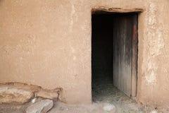 Vieux mur rural d'argile avec la porte en bois ouverte images libres de droits