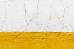 Vieux mur sale avec la peinture et le plâtre jaunes criqués Photographie stock
