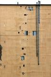 Vieux mur sale d'un bâtiment avec de petites fenêtres et cheminées Image libre de droits