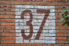 Vieux nombre à la maison, 37, au mur de briques Trente-sept Photo stock