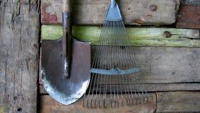 Vieux outils de jardin éventez le râteau et la pelle sur de vieux conseils en bois image libre de droits