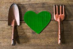 Vieux outils de jardinage rouillés grunges sales avec la feuille verte en forme de coeur sur le fond en bois grunge sale Image stock