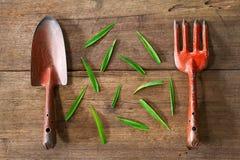 Vieux outils de jardinage rouillés grunges sales avec les feuilles vertes sur le fond en bois grunge sale Photographie stock libre de droits