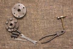 Vieux outils et détails rouillés sur le tissu rugueux Photo stock