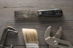 Vieux outils et pinceau sur le plancher Photographie stock
