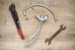 Vieux outils et robinet de tuyauterie sur le fond en bois photo libre de droits