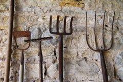 Vieux outils rustiques se penchant contre un mur en pierre Images libres de droits