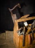 Vieux outils utilisés dans la boîte à outils Fond foncé Éclairage de tache Cadre en bois d'isolement photographie stock libre de droits