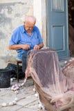 Vieux pêcheur réparant le filet de pêche Photo stock