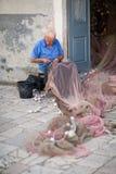 Vieux pêcheur réparant le filet de pêche Photographie stock libre de droits