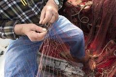 Vieux pêcheur réparant un trou en filet de pêche Image libre de droits