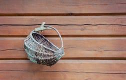 Vieux panier en osier accrochant sur le mur en bois Photo libre de droits