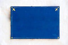 Vieux panneau-réclame bleu sur le mur blanc Photo libre de droits