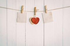Vieux papier deux en blanc et accrocher rouge de coeur Sur en bois blanc Images libres de droits