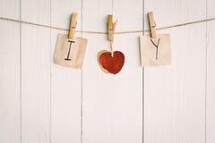 Vieux papier deux en blanc et accrocher rouge de coeur Sur en bois blanc Photos stock