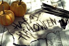 Vieux papier grunge avec le texte Halloween heureux de titre, les potirons et les bougies noires sur des planches photo libre de droits
