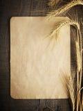 Vieux papier sur le fond en bois avec des oreilles de blé et de seigle Photo libre de droits