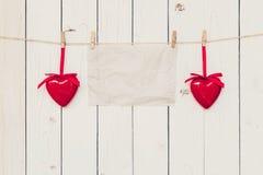Vieux papier vide et coeur rouge accrochant sur le fond en bois de conseil Photographie stock