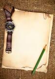 Vieux papiers et montre-bracelet Photographie stock libre de droits