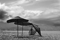 Vieux parasol noir et blanc sur la plage abandonnée Image libre de droits