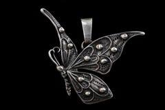 Vieux pendant dans la forme de papillon d'isolement sur le fond noir Photographie stock