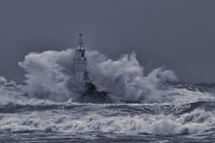 Vieux phare au milieu de grandes vagues orageuses La grande vague se brisante de mer contre des roches ?claboussent et pulv?risen photographie stock libre de droits