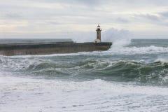 Vieux phare dans les vagues orageuses de mer Photos stock