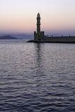 Vieux phare dans un port tranquille au coucher du soleil Photos stock