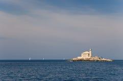 Vieux phare sur peu d'île Images stock