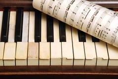 Vieux piano et feuille de cru avec des notes de musique Photographie stock