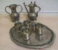 Vieux plats de bidon sur la cruche et le plat de tasse de plancher photo stock