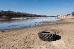 Vieux pneu de voiture jeté se trouvant sur la banque arénacée de la rivière images libres de droits