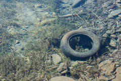Vieux pneu de voiture sous l'eau claire d'un lac de montagne vu pour Photos libres de droits