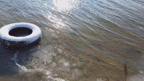 Vieux pneu sous la neige en sable de rivière dans l'horaire d'hiver banque de vidéos