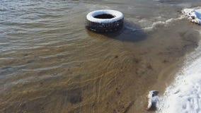 Vieux pneu sous la neige en sable de rivière dans l'horaire d'hiver clips vidéos