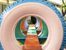 Vieux pneus avec la peinture colorée sur un terrain de jeu Photo stock