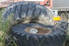 Vieux pneus très grands d'une machine de construction sur une décharge Photos stock