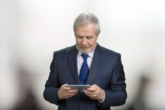 Vieux polititian tient le smartphone avec les deux mains images libres de droits