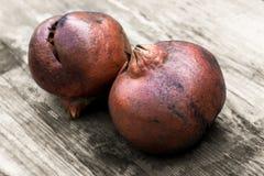 Vieux pomegranades sur une table Photographie stock libre de droits