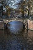 Vieux pont brun avec des vélos au-dessus du canal en automne Images stock