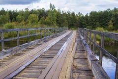 Vieux pont détruit de fond des planches et fer par la rivière de forêt Photos stock