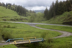 Vieux pont en bois au-dessus d'une crique dans la vallée d'une route de montagne Photographie stock