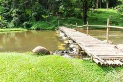 Vieux pont en bois au-dessus du courant avec la pelouse verte Photo libre de droits