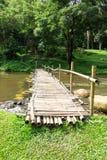 Vieux pont en bois au-dessus du courant avec la pelouse verte Photographie stock libre de droits